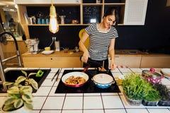 Jonge vrouw gebruikend wijn en kokend een gezonde maaltijd in huiskeuken Het maken van diner op keukeneiland die zich door induct royalty-vrije stock fotografie