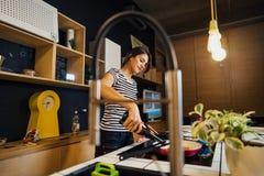 Jonge vrouw gebruikend wijn en kokend een gezonde maaltijd in huiskeuken Het maken van diner op keukeneiland die zich door induct stock fotografie