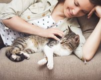 Jonge vrouw geknuffelkat thuis Royalty-vrije Stock Afbeeldingen