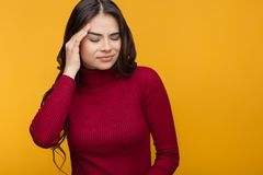 Jonge vrouw gekregen ziek en hoofdpijn op oranje achtergrond stock fotografie