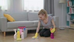 Jonge vrouw in gele handschoenen met doek schoonmakende vloer thuis in woonkamer stock footage