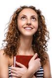 Jonge vrouw in gestreept vest met rood boek stock foto