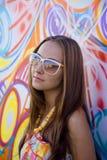 Jonge vrouw in glazen dichtbij graffitimuur Royalty-vrije Stock Foto