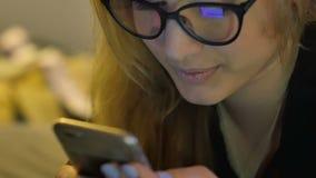 Jonge vrouw in glazen die mobiele telefoon met behulp van stock footage