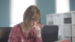 Jonge vrouw in glazen die op kantoor met muur die van rek werken, zijn hand zetten aan zijn lippen stock video