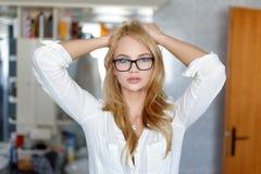 Jonge vrouw in glazen die thuis in badkamers stellen Stock Afbeelding