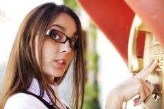 Jonge vrouw in glazen en gouden telefoon Stock Foto's
