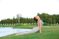 Jonge vrouw in grijze kostuum het praktizeren yoga Royalty-vrije Stock Foto's