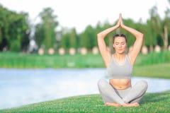 Jonge vrouw in grijze kostuum het praktizeren yoga Stock Afbeelding