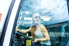 Jonge vrouw in haar functie als buschauffeur Stock Afbeeldingen