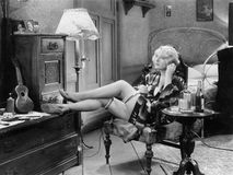 Jonge vrouw in haar slaapkamerzitting op een stoel met haar benen op een opmaker en een lijst met een paar flessen alcohol naast  Royalty-vrije Stock Foto