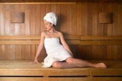 Jonge vrouw in handdoek het ontspannen op bank in sauna Stock Fotografie