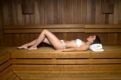 Jonge vrouw in handdoek het ontspannen op bank in sauna Royalty-vrije Stock Afbeeldingen