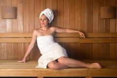 Jonge vrouw in handdoek het ontspannen op bank in sauna Stock Foto