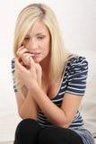 Jonge vrouw het bijten spijkers Stock Afbeelding