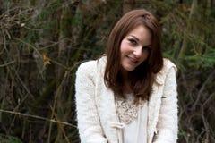 Jonge vrouw in het bos tijdens de winter het glimlachen Stock Afbeeldingen