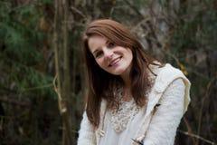 Jonge vrouw in het bos tijdens de winter het glimlachen Royalty-vrije Stock Afbeelding