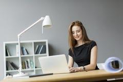 Jonge vrouw in het bureau Stock Afbeeldingen