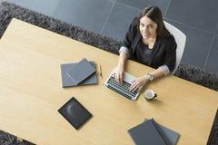 Jonge vrouw in het bureau Stock Foto's