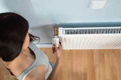 Jonge vrouw het draaien thermostaat op radiator Royalty-vrije Stock Afbeelding