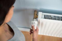 Jonge vrouw het draaien thermostaat op radiator Stock Afbeeldingen