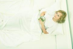 Jonge vrouw het drinken koffie in bed royalty-vrije stock afbeelding
