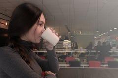 Jonge vrouw het drinken koffie in een koffie Het meisje warmt op een de herfstdag op met een hete drank Gang in het bedrijf of al royalty-vrije stock afbeeldingen