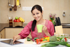 Jonge vrouw het drinken koffie in haar keuken Royalty-vrije Stock Afbeeldingen