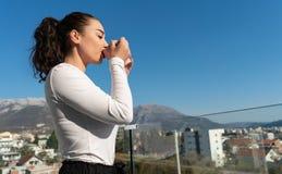 Jonge vrouw het drinken koffie of thee op balkon met mooi landschapspanorama stock fotografie