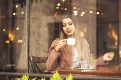 Jonge vrouw het drinken koffiezitting binnen in stedelijke koffie Vrij leuke meisje en holdingskop van koffie stock afbeeldingen