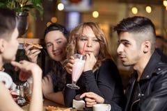Jonge vrouw het drinken milkshake terwijl het zitten met vrienden bij koffie royalty-vrije stock foto