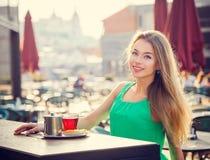 Jonge vrouw het drinken thee in een koffie in openlucht Stock Afbeeldingen
