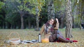 Jonge vrouw het drinken thee van een thermosfles in de zitting van het de herfstpark op een deken stock videobeelden