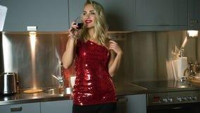 Jonge vrouw het drinken wijn in keuken stock videobeelden
