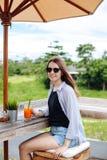 Jonge vrouw het drinken wortel smoothie bij openluchtbar Donkerbruin meisje die in groen mening en het drinken sap bij paraplu ge stock fotografie