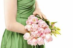 Jonge vrouw in het groene boeket van de kledingsholding van roze tulpen Stock Afbeelding
