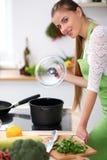 Jonge vrouw in het groene schort koken in de keuken De huisvrouw bereidt de soep voor Stock Fotografie