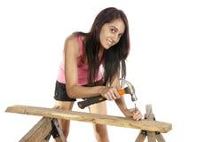 Jonge vrouw het hameren spijker in hout Stock Afbeelding