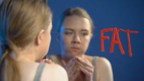 Jonge vrouw het kauwen doughnut, het afvegende glas van de woord vette spiegel, die wanorde, gezondheid eten stock video