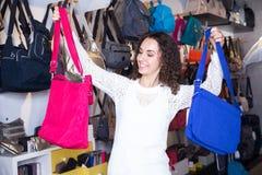 Jonge vrouw het kopen leerbeurs in herenmodezaakwinkel royalty-vrije stock afbeelding