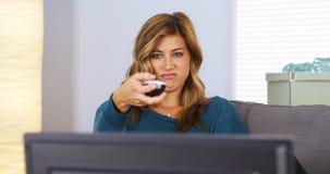 Jonge vrouw het letten op televisie met verre in hand royalty-vrije stock foto