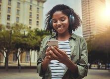 Jonge vrouw het letten op video die mobiele telefoon met behulp van stock foto