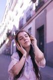 Jonge vrouw het luisteren muziek op de straat stock foto