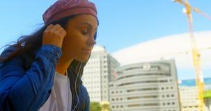 Jonge vrouw het luisteren muziek op hoofdtelefoons in de stad 4k stock videobeelden