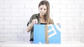 Jonge vrouw het openen doos met stationair mes stock video
