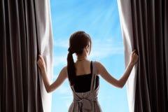Jonge vrouw het openen gordijnen en blauwe hemel Royalty-vrije Stock Fotografie