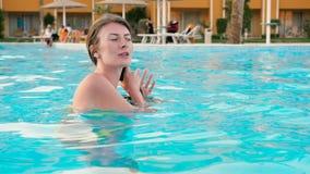 Jonge vrouw in het openlucht zwemmen in een pool HD stock videobeelden