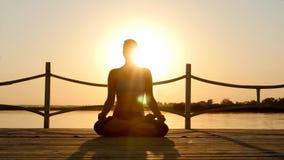 Jonge vrouw het praktizeren yoga bij zonsopgang