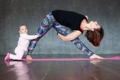 Jonge vrouw het praktizeren yoga, die zich in de oefening van Utthita bevinden Trikonasana royalty-vrije stock foto