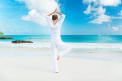 Jonge vrouw het praktizeren yoga op het strand stock foto's